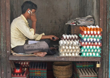 An egg seller chats on his cell phone in India, where dairy, egg and meat consumption has been on the rise. Courtesy of Meena Kadri, flickr.