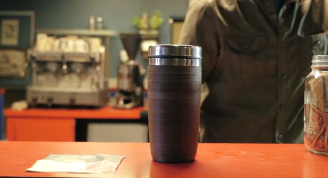 A to-go cup on a counter, made form coffee waste