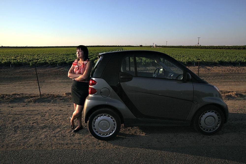 Melanie Gleason with her Smartcar near a Farm Field