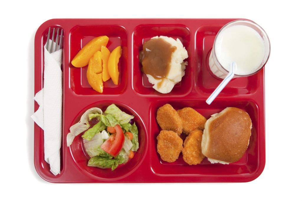 School lunch tray with food on white backgrounf
