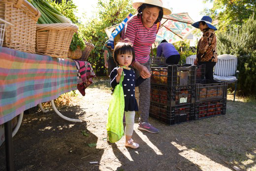 Locals pick up fruits and vegetables from the Free Farm Stand. Sometimes neighbors bring their own produce to share. YES! photo by Federica Armstrong.