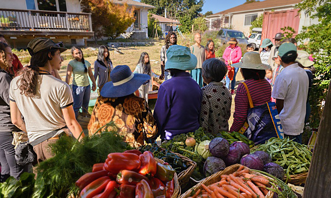 Oakland community members share a blessing before picking up produce from FrutaGift volunteers at Hidden Creek Cohousing in Fruitvale, California. When translators are present, the blessing is given in Spanish, English, Mandarin, Arabic, Mam, Japanese, and Catalan. YES! photo by Federica Armstrong