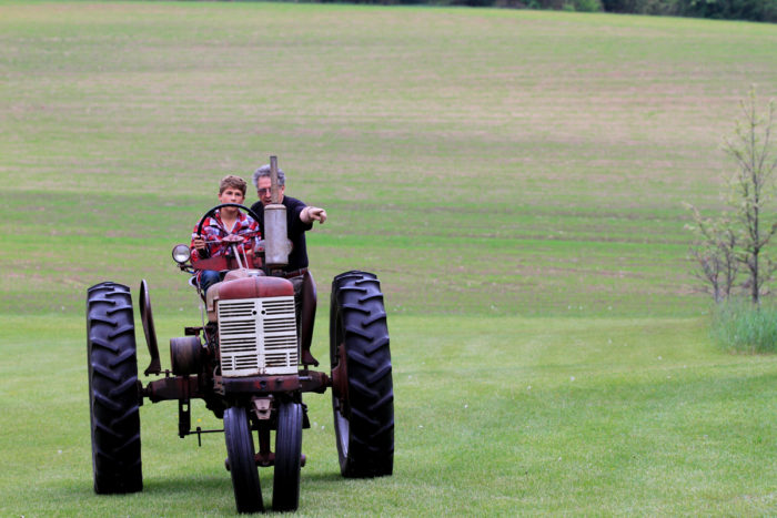 older farmer driving a young person around on a tractor