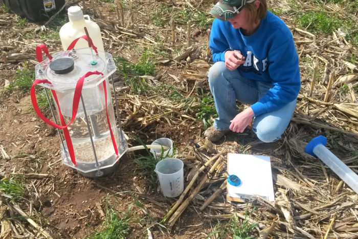 An Iowa State University student collects water infiltration data in a field with cover crops, as part of a Leopold Center supported research project. The project studied the long-term impact of cereal rye on cash crop yields, using data collected at 12 farms across the state for eight years.