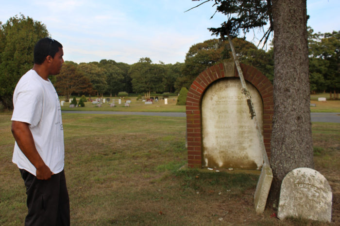 Shinnecock tribe member Shane Weeks visits the Shinnecock cemetery, looking at a memorial for the 10 Shinnecock men who died in the 1876 shipwreck of the Circassian off the coast of Mecox Bay in Bridgehampton. (Photo by Alexandra Talty)