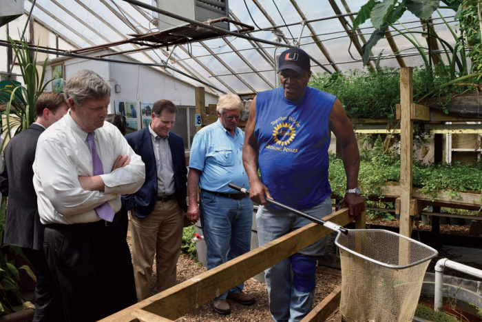Will Allen demonstrates his aquaculture system for Agriculture Secretary Tom Vilsack (left) in 2015. (Photo credit: USDA)