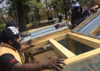 Xavier Brown, left, helps construct a wooden compost bin inside the Dix Street community garden in northeast Washington, D.C. (Photo by Kevon Paynter)