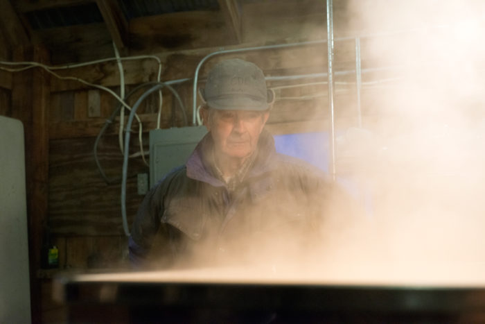 Buster Grant watches as a batch of maple sap boils down to syrup. Grant, 80, has been sugaring for half a century. He's skeptical about climate change, pointing out that Vermont weather is famous for being unpredictable. (Photo Credit: Chris Richard)