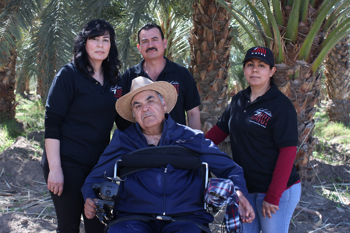 Enrique Bautista, owner of the Bautista Family Date Ranch, sits in front of his children Alicia (L), Alvaro (middle), and Maricela (R).
