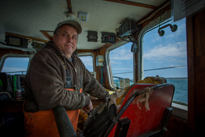 Captain Christopher Brown monitors activity on the back deck of the F/V Proud Mary while fishing in Rhode Island Sound. Photo © Ayla Fox for The Nature Conservancy
