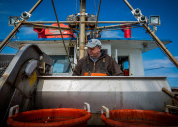 Captain Christopher Brown sorts fish at the F/V Proud Mary's conveyor, with the electronic monitoring cameras visible behind him. Photo © Ayla Fox for The Nature Conservancy