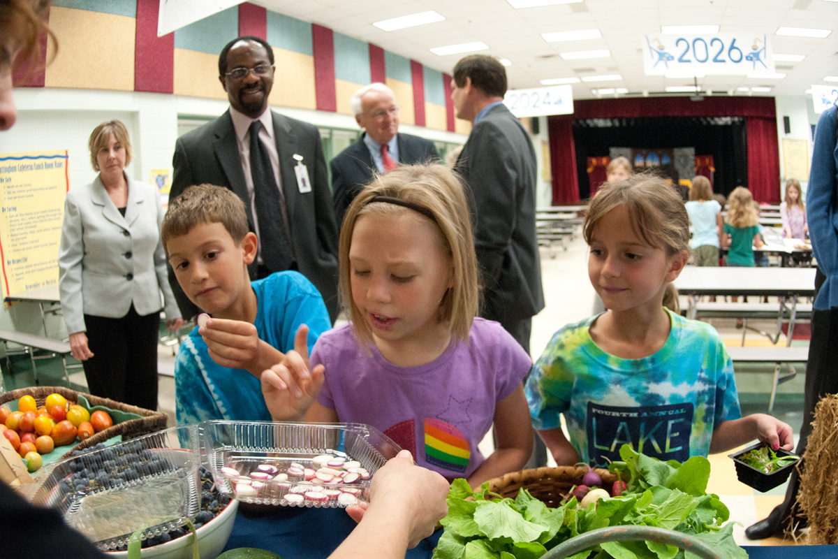 Students choosing salad from a school lunch salad bar.