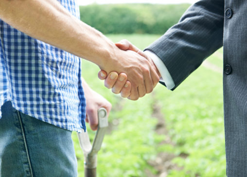 farmer and lawyer shaking hands in the field