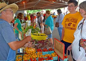 Farmer Joe Cooley Talks with Customer at the Mt. Pleasant Island Park Farmers Market. (Photo by Michigan Municipal League)
