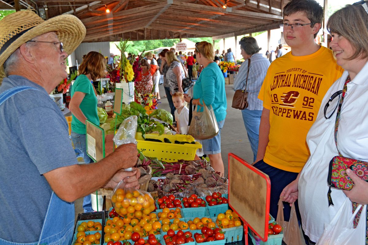 Farmer Joe Cooley Talks with Customer at the Mt. Pleasant Island Park Farmers Market. (Photo by Michigan Municipal League)