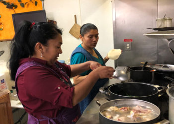 Rosa Hernandez prepares chicken for mole, while Sylvia Rojas makes tortillas -- about 70 a day. (Photo credit: Lisa Morehouse)