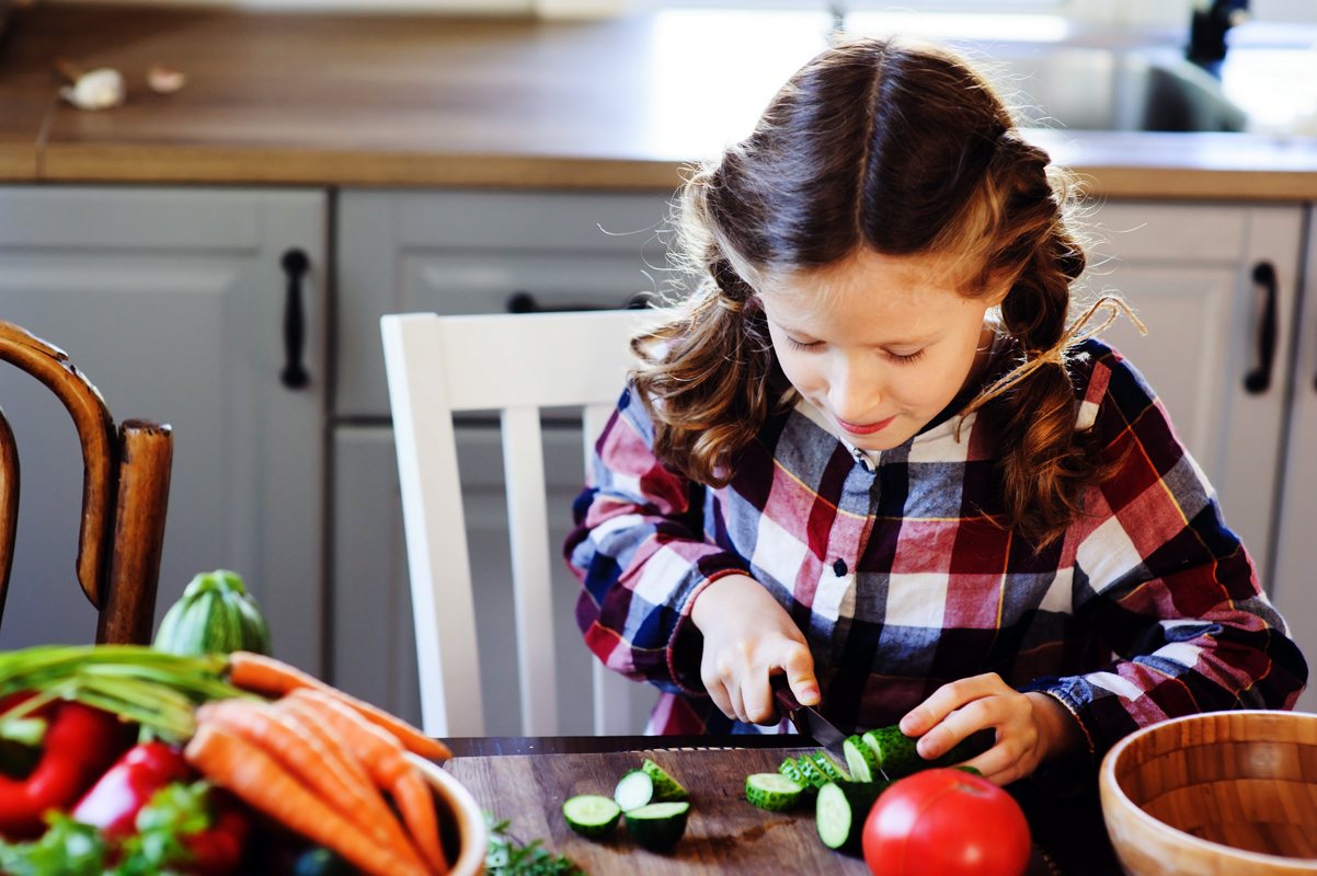young child cutting vegetables for salad