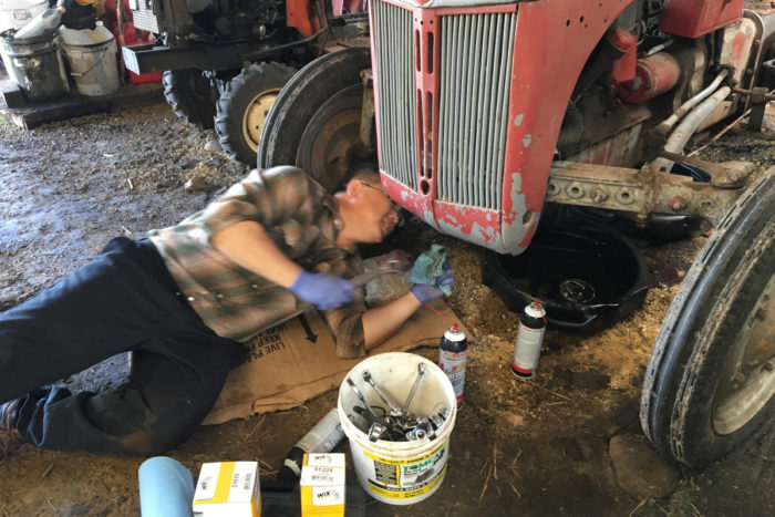 Blia and Phua's son Boun changes the oil in Thao's Garden's tractor.