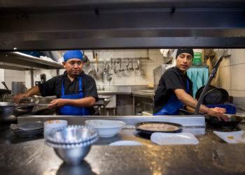 Dishwashers Esteban Soc, left, and Joselino Aguilar, right, at work in the kitchen of Mexican restaurant Caracol in Houston, Texas on July 12, 2017.