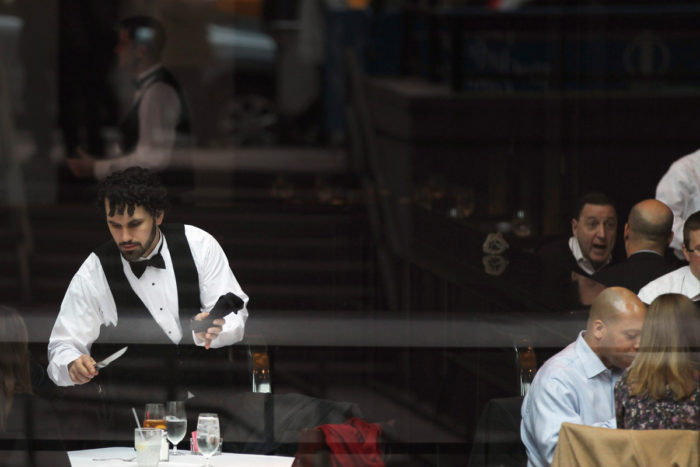 A waiter clears a table at a midtown restaurant popular for business lunches on November 22, 2011 in New York City.