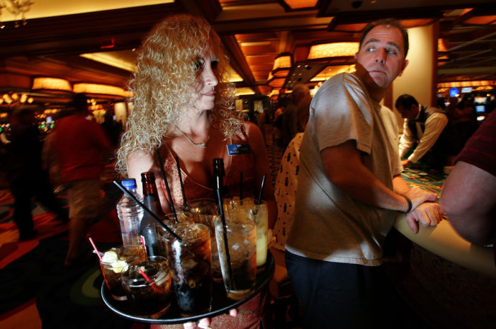 A female server passes a male customer. Photo courtesy of KCET.