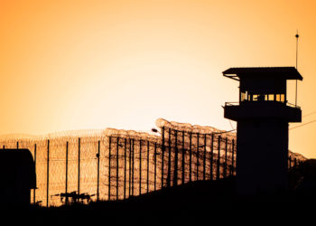 Prison guard tower and high fence.