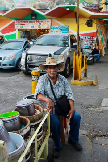 A man selling traditional drinks sits outside Mercado Medellín in Mexico City.