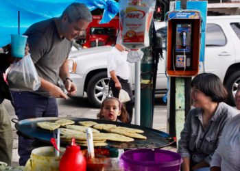 Mexicans gather at a street corner comal for lunch in the milpa tradition.