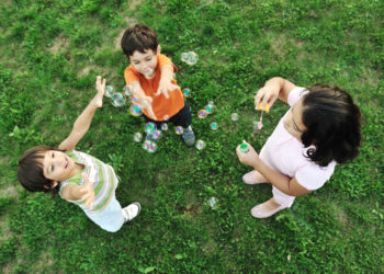 Small group of happy children making bubbles and playing together in nature