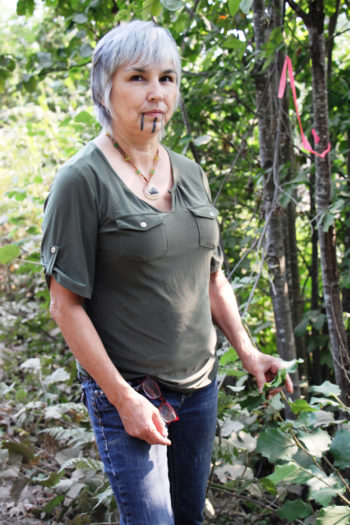 Margo Robbins is surprised by the growth of hazel sprouts, a mainstay of Yurok basketweavers, in the months since she and others intentionally burned this area.