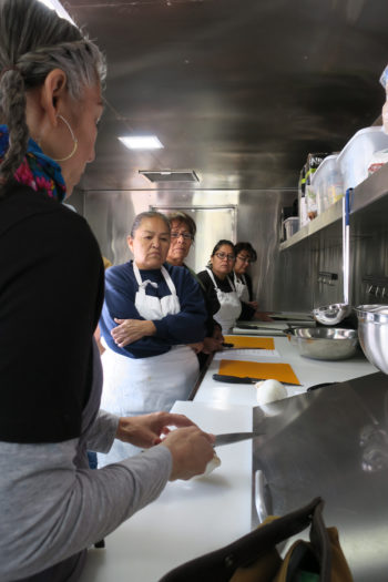 Chef Felicia Cocotzin Ruiz demonstrates how to properly hold a knife on the Mobil Unit for Training and Nutrition (MUTN). Photo courtesy of Felicia Cocotzin Ruiz.