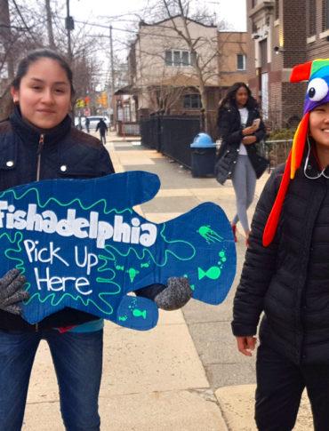 "Eleventh graders Michelle Martinez, (left) and Cing ""Jenny"" Lian, greet Fishadelphia customers. (Photo credit: Erme Maula for fishadelphia)"