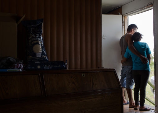 A farmworker couple, Nelson and Silvia* from Guatemala, surveys the flooding outside of their North Carolina trailer home after Hurricane Florence. (Photo by Justin Cook.)