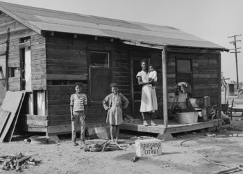 A Black family standing outside their home. Photo © Ernest Lowe