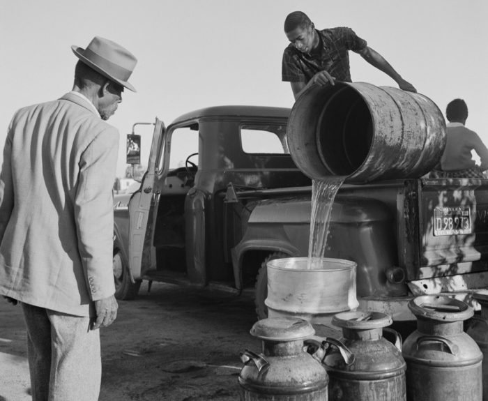Pouring water for migrant farmworkers. Photo © Ernest Lowe