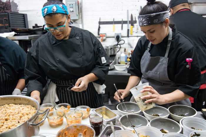 "Brit Reed (left) cooks during I-Collective's 2017 NYC Thankstaking pop-up series. (Photo © <a href=""https://gardenwarriorsgoodseeds.com/"">Elizabeth Hoover</a>)"