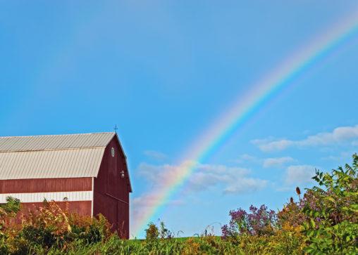 a rainbow over a farm and barn