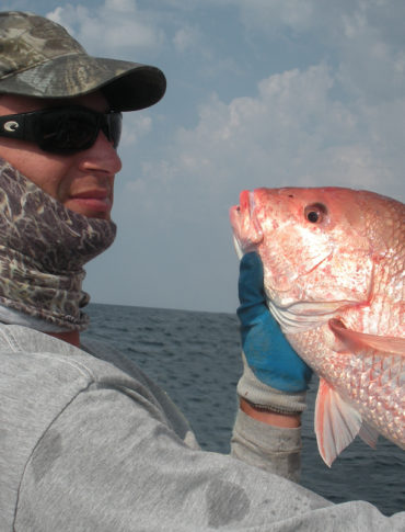 A Florida Fish and Wildlife Conservation Commission staffer poses with a red snapper. (Photo CC-licensed by FWC)
