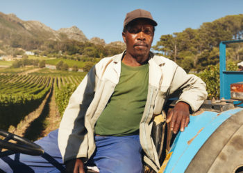 black farmer sitting on a tractor