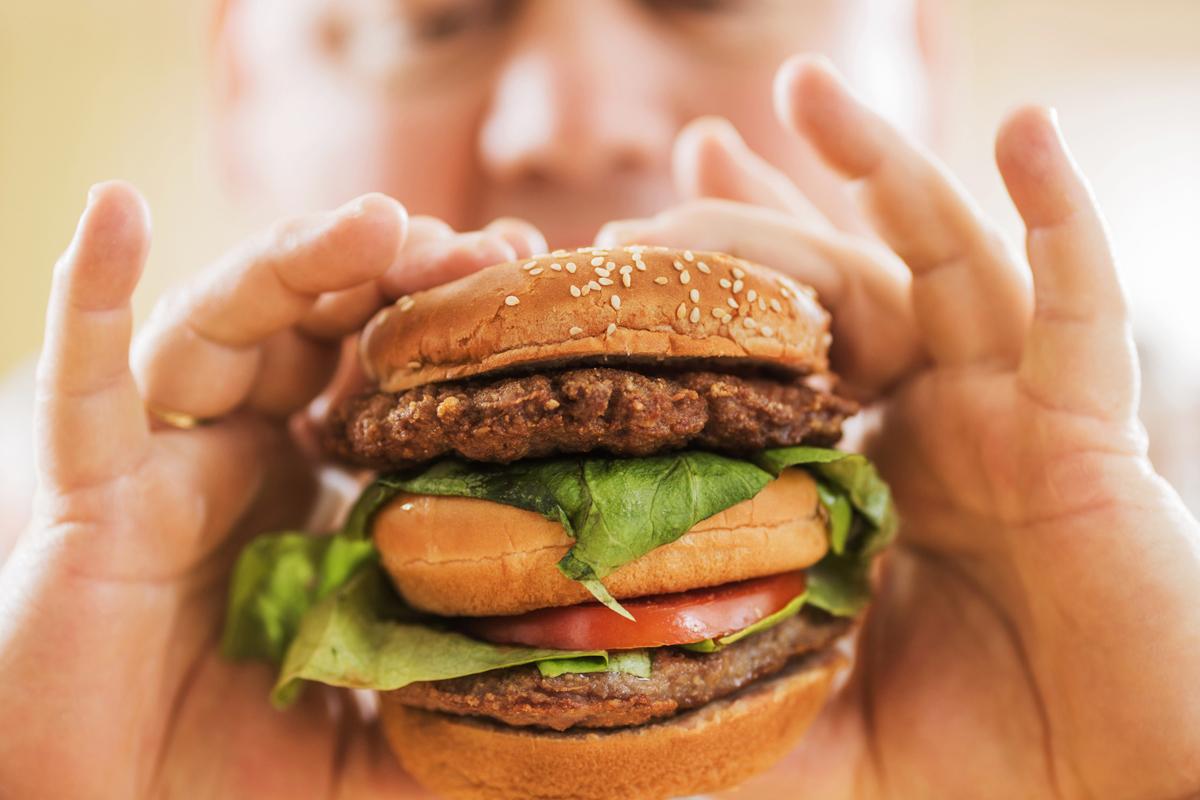 a person eating a large hamburger
