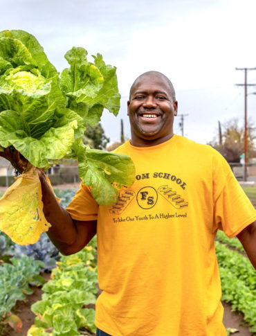 Rev. Floyd D. Harris Jr. harvests cabbage from Freedom School Fresno's demonstration farm. (Photo © Joan Cusick)
