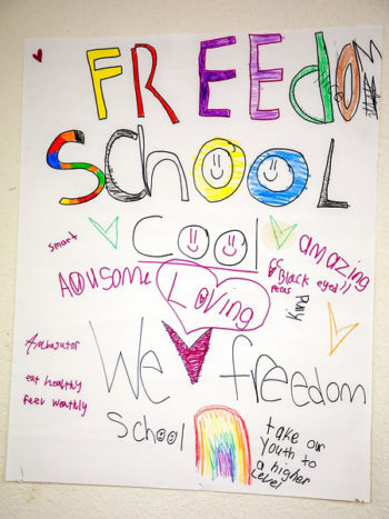 A student poster for Freedom School hangs in the multipurpose room, where classes are held. (Photo © Joan Cusick)