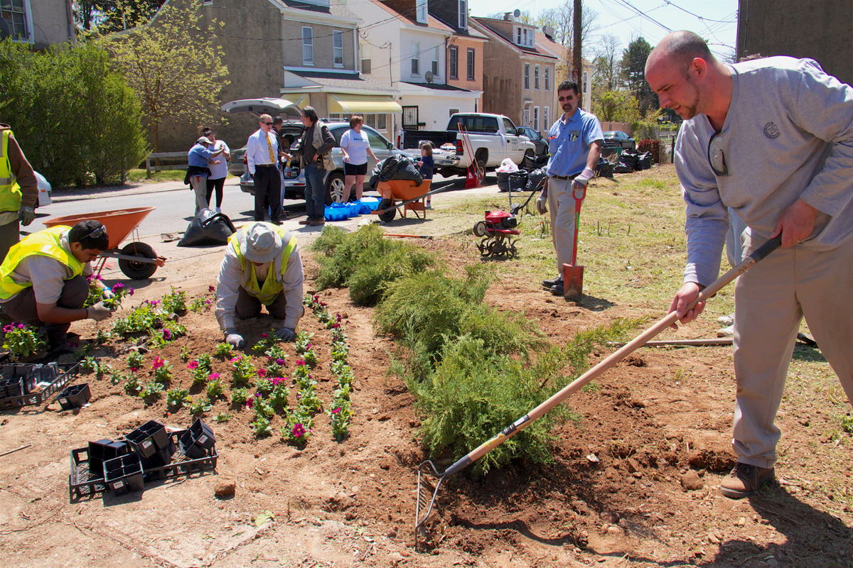 Volunteers plant a small ornamental garden at the corner of a newly cleaned vacant lot in Philadelphia.