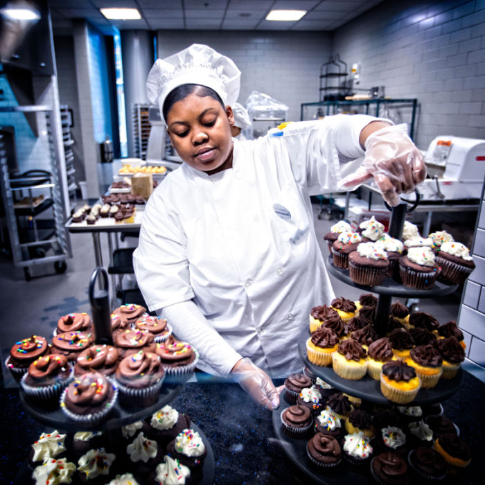 A UK Dining employee fills the pastry station at Champions Kitchen with cupcakes made from Kentucky's Weisenberger Mill flour. (Photo courtesy of University of Kentucky)