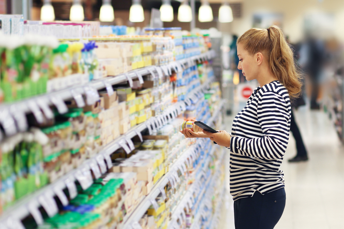 woman shopping for food in a grocery store and looking at ingredients labels
