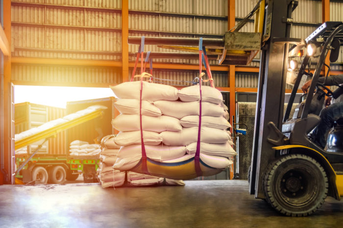 forklift loading large bags of sugar for transportation in a warehouse
