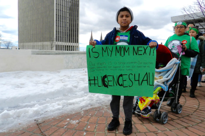 A young child holding up a sign urging for driver's licenses for all