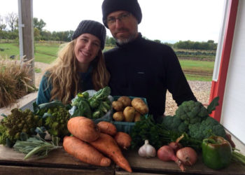 Melissa and Andy Dunham with a weekly CSA share from their farm. (Photo courtesy of Grinnell Heritage Farm)