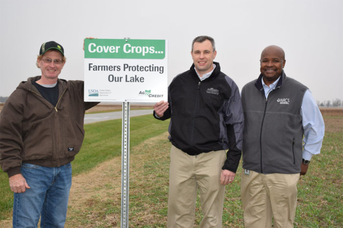 Hardin County, Ohio, farmer Jerry McBride (left) place the first cover crop sign on his field planted with crop field which contains a mix of oilseed radish, hairy vetch, and cereal rye, as part of an NRCS EQIP program. USDA NRCS photo by Dianne Johnson.