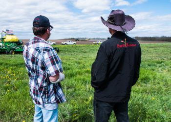 A Farm Rescue volunteer stands with a farmer getting help from the nonprofit.